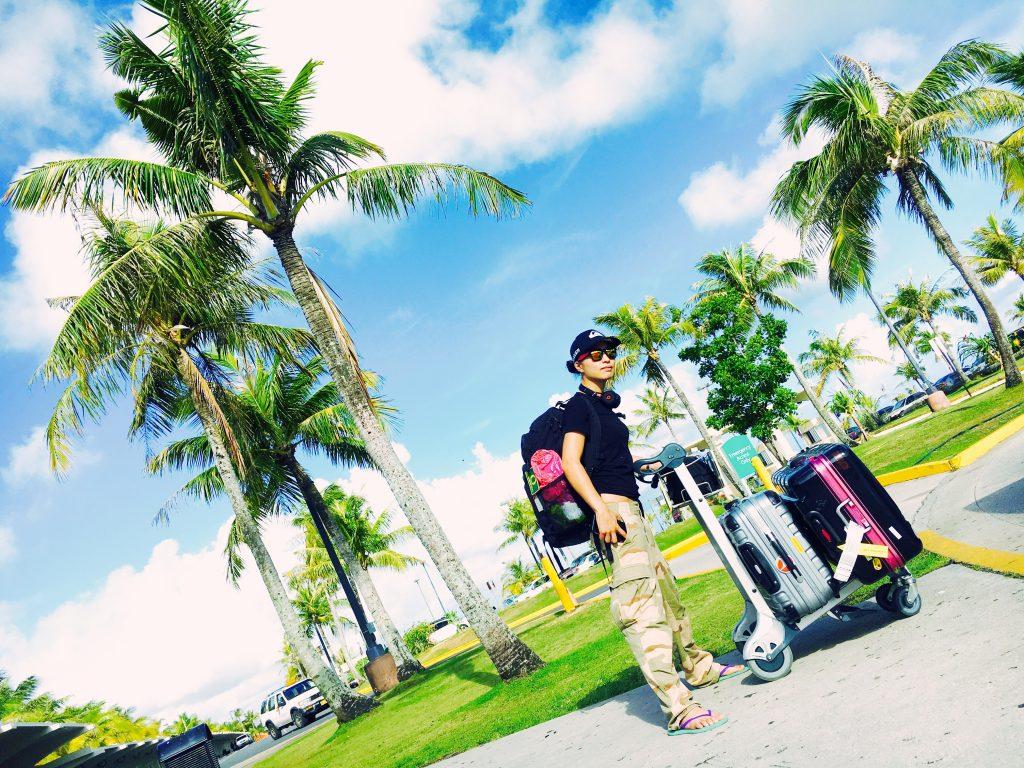 グアムの空港の椰子の木の前でタクシーを待つ