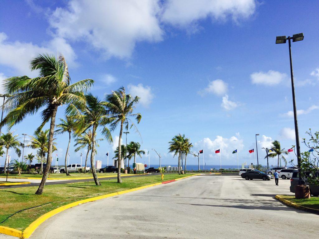 晴天の日のグアムの空港の駐車場と国旗
