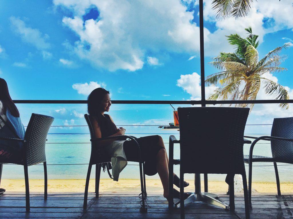 グアムの椰子の木の見えるカフェに座る